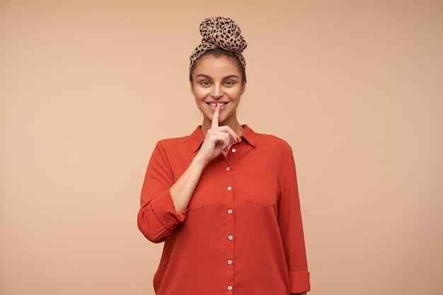 Positive junge attraktive braunhaarige dame mit natürlichem make-up, das zeigefinger auf ihren lippen hält, während sie bittet, sie geheim zu halten und froh zu lächeln, isoliert über beige wand
