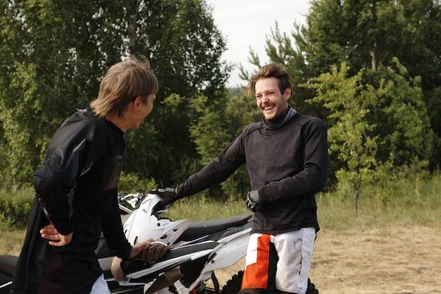 Positive junge biker, die motorräder halten, während sie nach rennen im wald plaudern und lachen