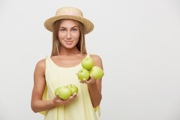 Positive junge blauäugige blonde frau mit natürlichem make-up, das augenbrauen anhebt, während kamera mit gefalteten lippen betrachtet wird, die über weißem hintergrund mit grünen äpfeln in erhobenen händen stehen