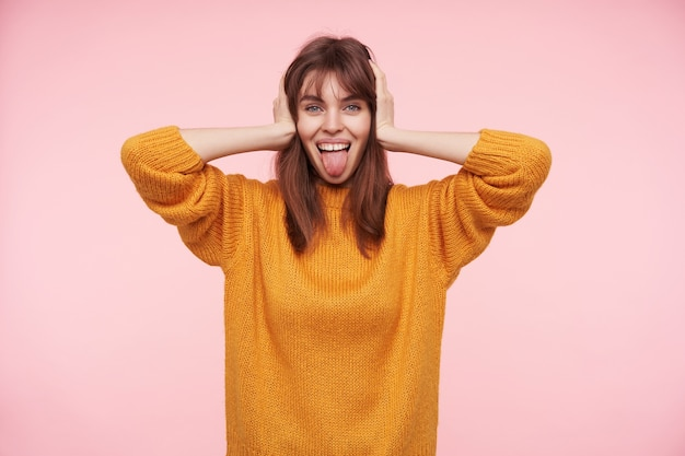 Positive junge blauäugige dunkelhaarige dame, die ihre ohren mit erhobenen handflächen bedeckt und fröhlich aussieht, ihre zunge herausstreckt, während sie über rosa wand posiert