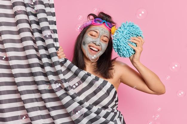 Positive junge brünette asiatische frau mit dunklem haar lächelt freudig kippt kopf nimmt dusche im badezimmer genießt hygieneverfahren wendet tonmaske hält schwamm hält schwamm zum waschen des körpers macht frisur