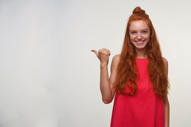 Positive junge charmante lesekopfdame im rosa kleid, die ihr rotes welliges haar im knoten trägt, über weißem hintergrund mit erhobenem daumen aufwirft und beiseite zeigt, freudig zur kamera lächelnd