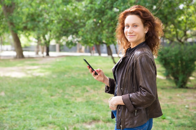 Positive junge dame, die smartphone im stadtpark verwendet