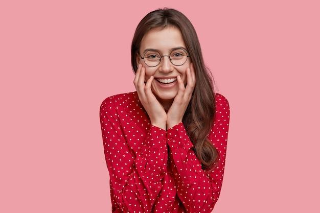Positive junge dame mit sanftem lächeln, trägt eine brille, modisches hemd, zeigt natürliche schönheit