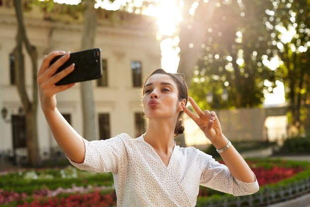 Positive junge dunkelhaarige frau mit lässiger frisur, die lippen im luftkuss faltet und hand mit siegesgeste hebt, während foto von sich auf ihrem handy macht