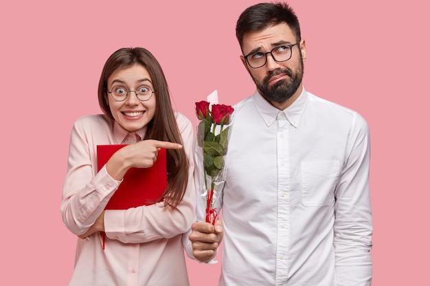 Positive junge europäische frau trägt rotes lehrbuch, zeigt auf ungeschickten bärtigen mann im weißen hemd, der sich schüchtern fühlt, schönen blumenstrauß hält, liebesgeschichte hat