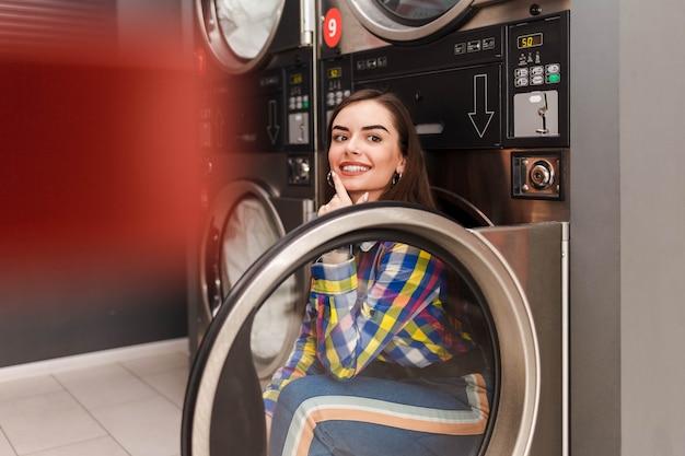 Positive junge frau, die auf der trocknermaschine im selbstbedienungswäscher sitzt