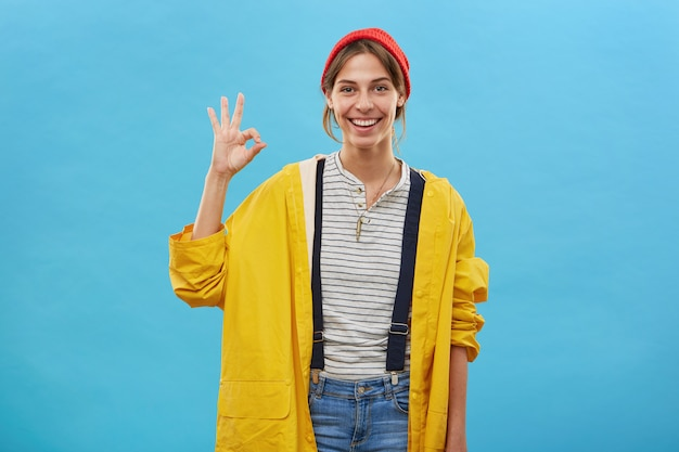Positive junge frau, die beiläufig gekleidet zeigt okes zeichen mit hand, die etwas genehmigt. frau in der losen gelben jacke und im roten hut lokalisiert über blaue wand, die mit der hand gestikuliert. fröhliche arbeiterin