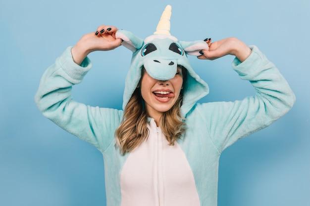 Positive junge frau, die im lustigen pyjama aufwirft