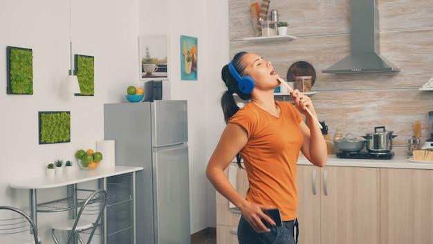 Positive junge frau, die morgens auf holzlöffel singt. energiegeladene, positive, fröhliche, lustige und süße hausfrau, die alleine im haus tanzt. unterhaltung und freizeit allein zu hause