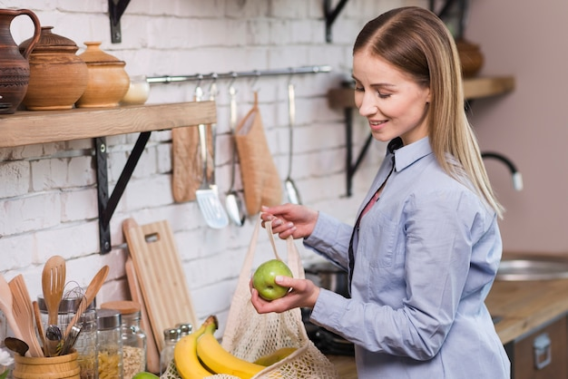 Positive junge frau, die organische früchte aus dem beutel nimmt