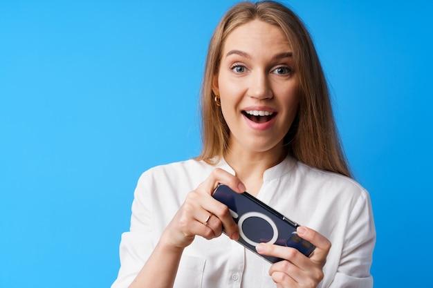 Positive junge frau, die spiele auf dem smartphone vor blauem hintergrund spielt Premium Fotos