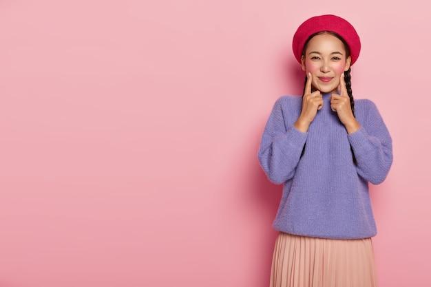 Positive junge frau hält vorderfinger auf beiden wangen, ist in hochstimmung, trägt rote baskenmütze, lila pullover und rock, steht über rosa wand
