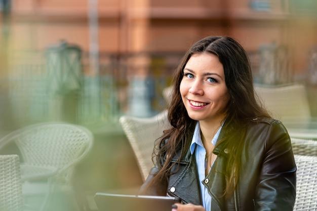 Positive junge frau in der freizeitkleidung, die im straßencafé sitzt, während sie an entferntem projekt auf digitalem tablett arbeitet