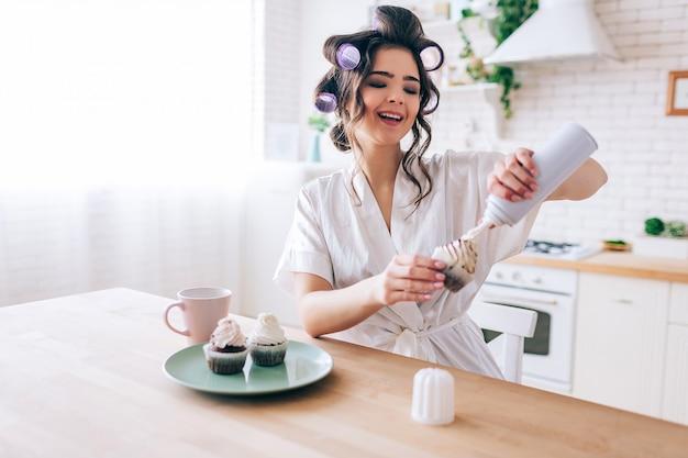 Positive junge frau legte weiße creme auf pfannkuchen und lächelte. weibliche haushälterin sitzen am tisch in der küche. das leben ohne arbeit genießen. sugar daddy zahlt für alles. lockenwickler im haar.