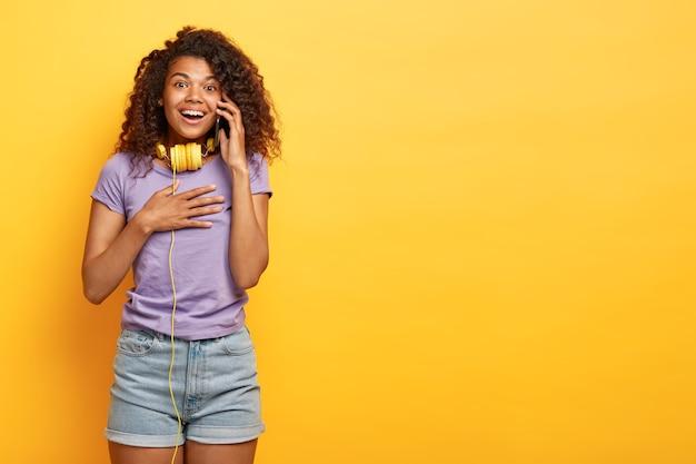 Positive junge frau mit afro-frisur, die gegen die gelbe wand aufwirft