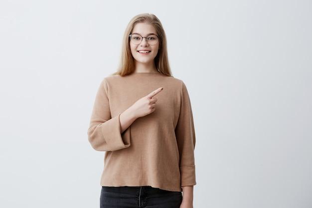 Positive junge frau mit blonden haaren, braunem pullover und brille, hat gesunde haut, angenehmes lächeln, zeigt auf kopienraum auf grauem hintergrund. sieh dir das an! werbekonzept