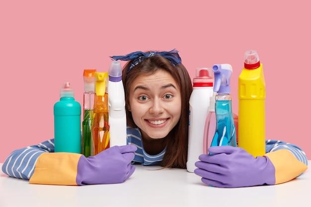 Positive junge frau mit entzücktem ausdruck, zahnigem lächeln, umarmt chemische reinigungsmittel, sieht fröhlich aus