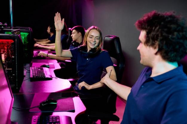 Positive junge frau mit kopfhörern um den hals, die dem verbündeten des videospiels fünf geben, während sie mit ihm im computerclub erfolg feiern