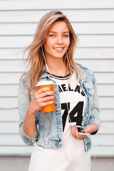 Positive junge frau mit natürlichem make-up mit einem schönen lächeln in einer trendigen blauen jeansjacke in einem weißen t-shirt, das eine tasse kaffee in ihrer hand hält