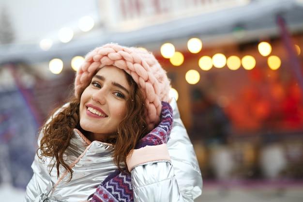 Positive junge frau mit silbernem mantel und strickmütze, die winterferien genießt. platz für text