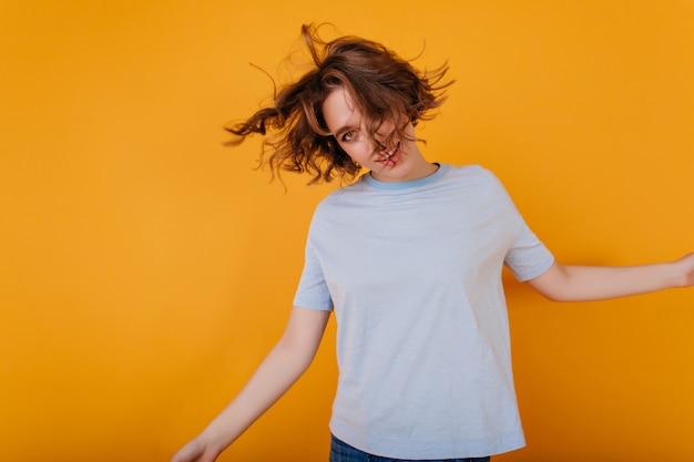 Positive junge frau mit trendigem haarschnitt, der im blauen t-shirt tanzt