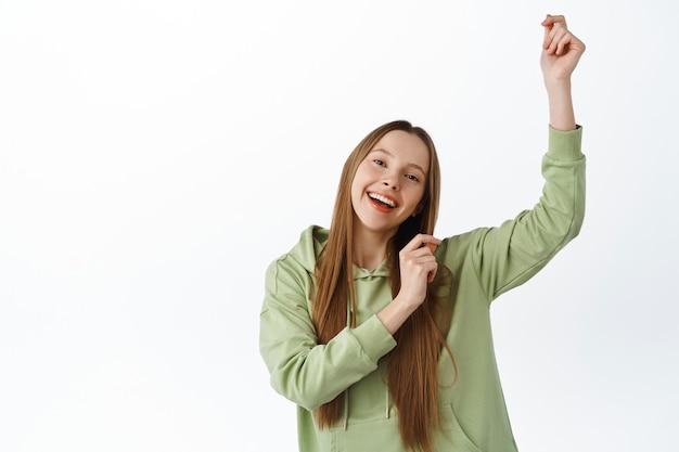 Positive junge frau tanzt und hat spaß, trägt einen lässigen hoodie, feiert mit tanz, lächelt fröhlich, weiße wand