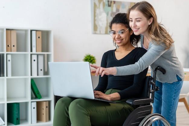 Positive junge frauen, die an einem laptop arbeiten