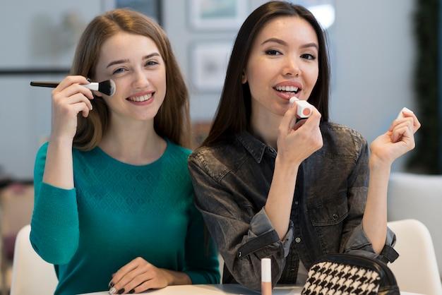 Positive junge frauen, die make-up-accessoires versuchen