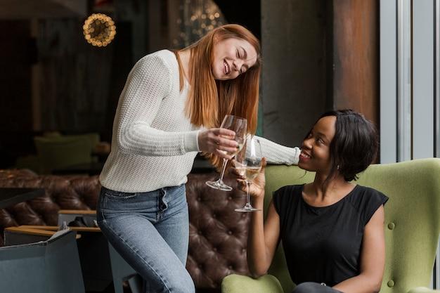 Positive junge frauen, die zusammen wein trinken