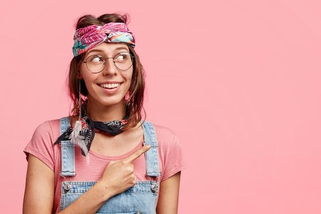 Positive junge hippie-frau mit freudigem ausdruck zeigt beiseite, gekleidet in stilvolles stirnband und jeansoverall