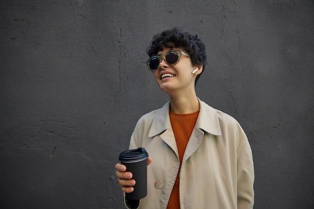 Positive junge hübsche dunkelhaarige dame mit kurzen lockigen haaren, die ein trendiges outfit und eine stilvolle sonnenbrille tragen, während sie die straße entlang gehen und heißen kaffee trinken, bevor sie mit dem arbeitstag beginnen