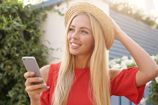 Positive junge hübsche langhaarige blonde frau, die mit charmantem lächeln beiseite schaut und smartphone in erhobener hand hält, während sie gegen hinterhof steht