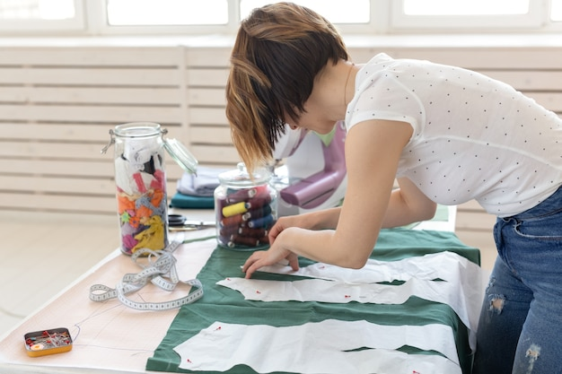 Positive junge hübsche mädchen näherin designerin arbeitet an einem neuen projekt, während an ihrem schreibtisch mit einer nähmaschine in ihrer werkstatt sitzen. kreatives geschäftskonzept.