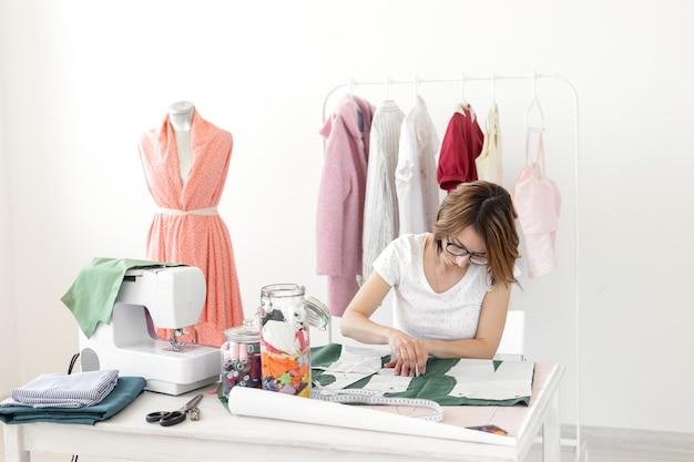 Positive junge hübsche mädchen näherin designerin arbeitet an einem neuen projekt, während an ihrem schreibtisch mit einer nähmaschine in ihrer werkstatt sitzen.