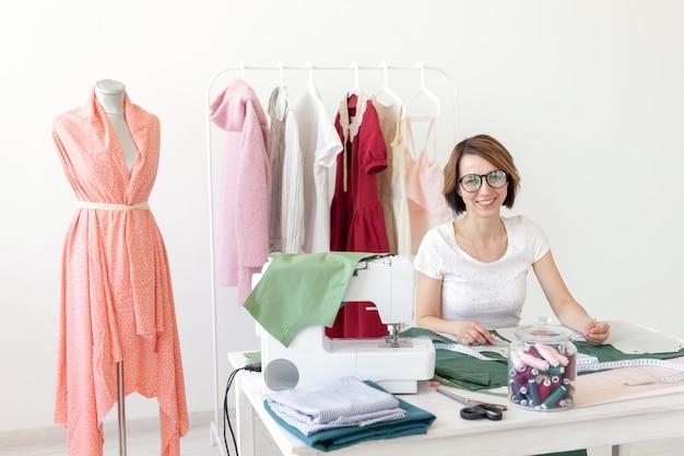 Positive junge hübsche näherin-designerin, die an einem neuen projekt arbeitet, während sie an ihrem schreibtisch sitzt