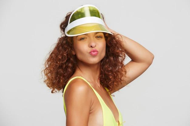Positive junge hübsche rothaarige lockige dame, die lippen im luftkuss faltet und hand zu ihrer neonmütze hebt, während sie über weißem hintergrund steht und mit freunden zur strandparty geht