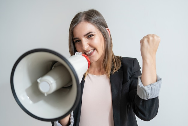 Positive junge kaukasische frau mit dem megaphon, das erfolg zeigt