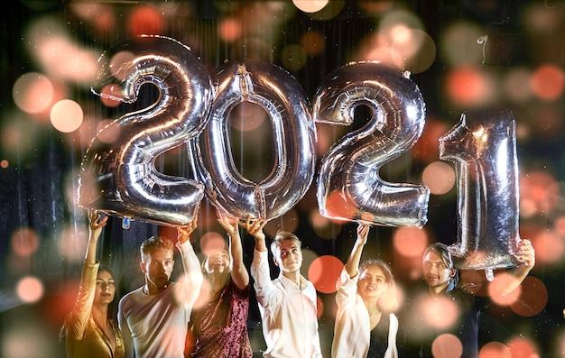 Positive junge leute halten ballons mit dem neuen 2021-jahr und feiern.