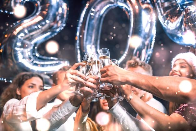 Positive junge leute halten ballons mit neuem 202-jahr und feiern.
