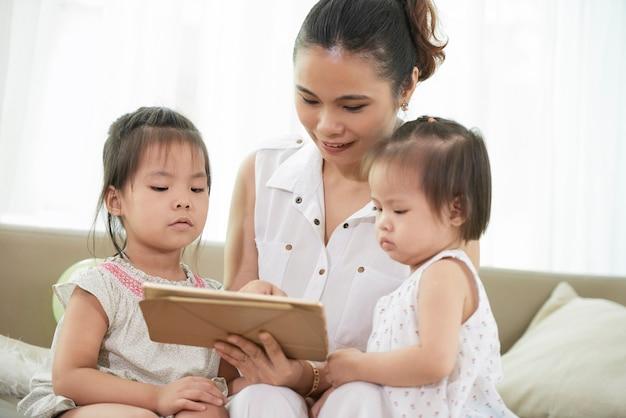 Positive junge mutter, die der kleinen tochter erklärt, wie man ein spiel auf einem digitalen tablett spielt