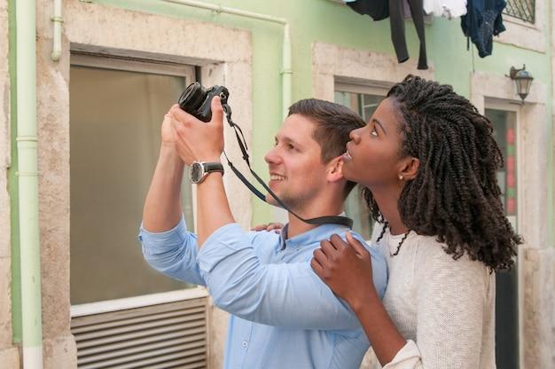 Positive junge paare, die fotos auf kamera in der stadt machen