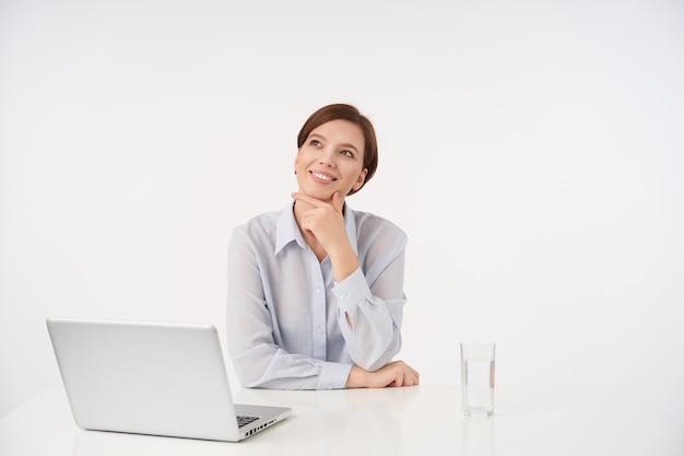 Positive junge schöne braunhaarige frau mit kurzem, trendigem haarschnitt, der sanft ihr kinn berührt, während sie verträumt nach oben schaut und angenehm lächelt, während sie auf weiß sitzt