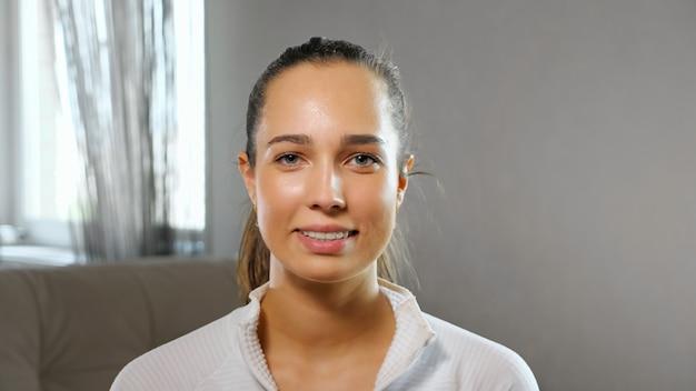 Positive junge sportlerin bloggerin im weißen sweatshirt lächelt für die kamera in einem hellen, geräumigen zimmer zu hause in der nähe der zeitlupe posieren