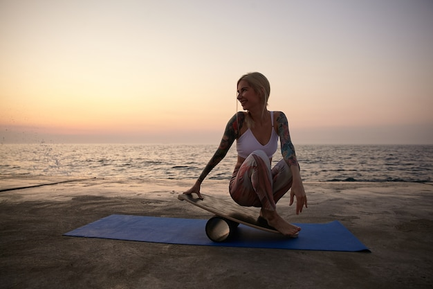 Positive junge tätowierte frau in guter körperlicher verfassung, die über meerblick aufwirft, auf sportmatte sitzt und sich auf balancebrett stützt, sport am frühen morgen am meer macht