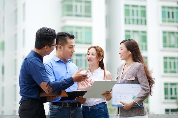 Positive junge vietnamesische finanzabteilungsleiter diskutieren nachrichten und berichte, wenn sie im freien stehen