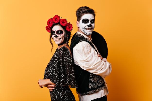 Positive jungen und mädchen lächeln aufrichtig. foto des paares mit halloween-make-up in großer stimmung auf orange wand.
