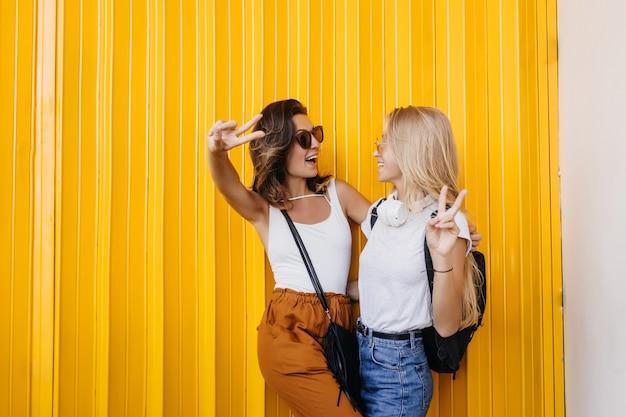 Positive kaukasische frauen, die einander während des fotoshootings auf gelbem hintergrund betrachten.