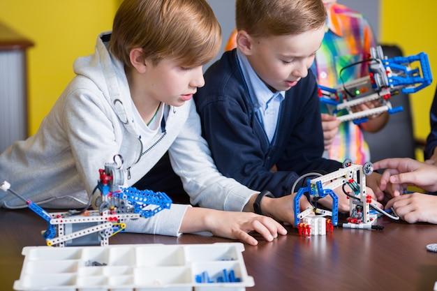 Positive kinder spielen und montieren den konstrukteur im kinderzimmer.