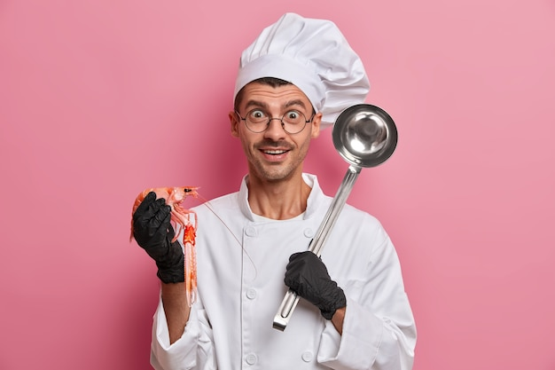 Positive kochposen mit ungekochten krebsen, stahlkelle, die leckere suppe zubereiten, tragen weiße uniform